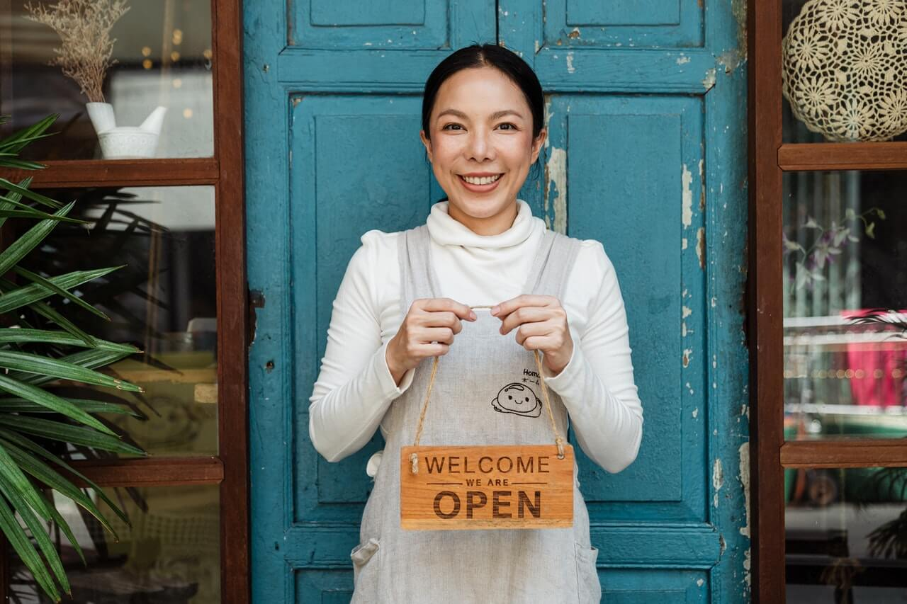 business owner holding a sign that says welcome we are open